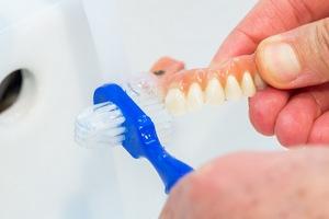 Czy i jak można wybielić protezę zębową domowym sposobem? [fot. czyszczenie protezy zębowej]